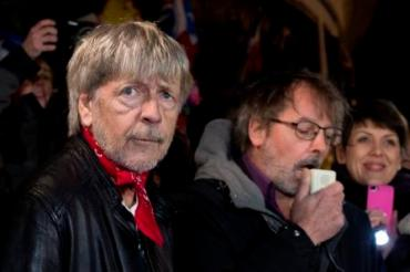 French singer Renaud (L) and French humorist Christophe Aleveque (C) take part in a homage to the victims of the January 2015 Paris attacks, on the Place de la Republique on January 7, 2016 in Paris. France holds official ceremonies marking a year since a jihadist attack on the offices of Charlie Hebdo, with the French satirical magazine defiantly reasserting its provocative spirit. / AFP / KENZO TRIBOUILLARD